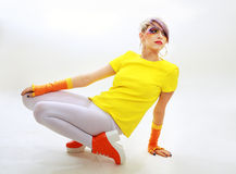 Grunge girl down floor. Fashion glamour grunge girl in yellow with creative paint make up sitting down the floor Stock Photo