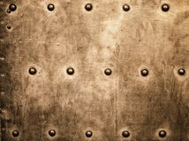 Grunge gold brown metal plate rivets screws background texture. Closeup of grunge gold brown metal plate with rivets and screws as background or texture Royalty Free Stock Photo