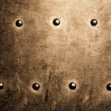 Grunge gold brown metal plate rivets screws background texture Royalty Free Stock Photos