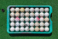 Grunge golf balls in tray on green Royalty Free Stock Photos