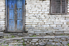 Grunge gray bricks house wall with blue door and window Royalty Free Stock Photography
