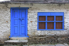 Grunge gray bricks wall with blue door and window of Nepal house royalty free stock images