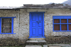 Grunge gray bricks wall with blue door and window of Nepali house Stock Photos