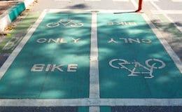 Grunge green bicycle lane on asphalt road Stock Images