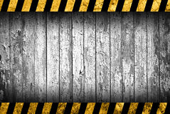 Grunge grey wood background with warning stripes. Grunge grey wood background with black and yellow warning stripes Royalty Free Stock Images