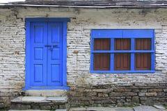 Grunge grijze bakstenen muur met blauw deur en venster van hous van Nepal Royalty-vrije Stock Afbeeldingen