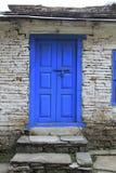 Grunge grijze bakstenen muur met blauwe deur van Nepali-huis Royalty-vrije Stock Afbeeldingen