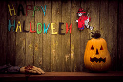 Grunge Happy Halloween background. Jack pumpkin head with spider, witch, severed hand and an inscription on a wooden background Happy Halloween royalty free stock image