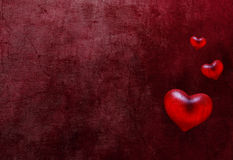 Grunge hearts. Scratched dark background with three red hearts Stock Image