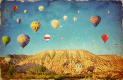 Grunge image  of colorful hot air balloons against blue sky in C Stock Images