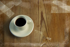 Grunge image of cup of coffee on table. Grunge image of cup of espresso coffee on a wooden vintage table with tape stuck on it Royalty Free Stock Photo