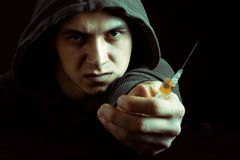Grunge image of a depressed drug addict looking at a syringe and drugs Royalty Free Stock Photography