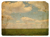 Grunge image of a field and sky with clouds. And spots. Vintage background Royalty Free Stock Photos