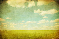 Grunge image of green field and blue sky. With white clouds Stock Photography