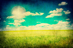 Grunge image of green field and blue sky Royalty Free Stock Photography