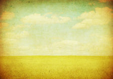 Grunge image of green field and blue sky Stock Image