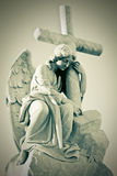 Grunge image of a sad angel holding a cross. In greenish shades Stock Photo