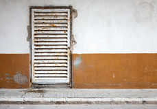 Grunge interior background with concrete wall and metal door Stock Photos