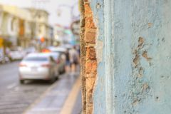 Grunge light blue walls that the cement was broken until they saw the bricks inside. The background is street and walkway. Concept stock photos