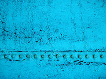 Grunge Line. Close-up of old, cracked, dirty teal paint with the black base showing through and a line of bolts running across the surface Royalty Free Stock Photography