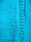 Grunge Line. Close-up of old, cracked, dirty teal paint with the black base showing through and a line of bolts running across the surface Royalty Free Stock Photos