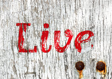 Grunge live wooden sign. Old wooden sign with live in red letters and two rusty bolts Royalty Free Stock Images