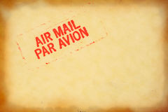 Grunge mail stamp. Air mail stamp on vintage yellow worn envelope with copyspace Stock Photography