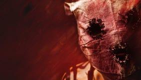 Grunge Masked Killer. Evil looking masked man on a red grunge background stock photo