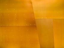 Grunge Metal Background. Section of bronze colored riveted metal plates Royalty Free Stock Image