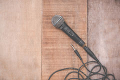 Grunge microphone with cable on wooden background Royalty Free Stock Photo