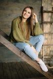 Grunge moda: ślicznej młodej dziewczyny nieformalny model w niebieskich dżinsach, zmrok dział pulower i białe skarpety siedzi na  zdjęcie stock
