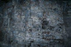 Grunge mystical gray-blue layered rock wall with uneven surface. Grunge mystical gray-blue layered rock wall with uneven hollowed surface stock photo