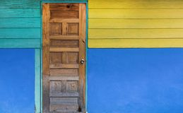 Grunge old door with color painted wall. Classical vintage and Modern Interior concept. Architecture and Home design theme. Style, wooden, yellow, blue stock photo