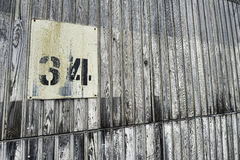 Grunge old wall with number 34. At an old abandoned warehouse hangs a number on the wall. The number is 34 Stock Photography
