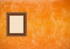 Grunge orange Stuckwand mit leerem Bilderrahmen Stockbild