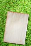Grunge paper on green grass Stock Photo