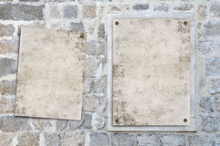 Grunge paper on the wall. Two blank grunge paper on the old stone wall Royalty Free Stock Image