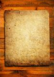 Grunge paper on wood plank Royalty Free Stock Images