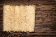 Old Vintage Paper with Torn Edge on Brown Wood Planks royalty free stock photo