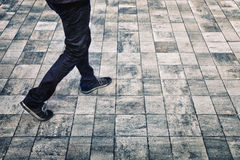 Grunge pedestrian city walking. Grunge city walking background with man feet. Grunge filter effect used Royalty Free Stock Photo