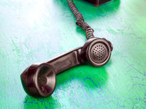 Grunge phone receiver from around 1970. Grunge telephone receiver from around 1970 on cracking and peeling green surface Royalty Free Stock Photography