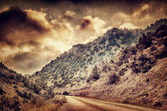 Grunge photo of road in the mountains Royalty Free Stock Photo