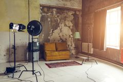 Grunge photo studio in old room. Photo studio interior. Photo equipment. Empty studio with aged walls and furniture stock image