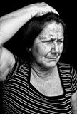Grunge portrait of an old woman with a headache Royalty Free Stock Images
