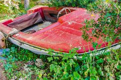 Vintage boat, ancient red motorboat at shore. Grunge red ancient motor boat, old retro nautical vessel royalty free stock photo