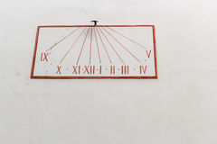 Grunge red sundial on pastel wall Stock Photo
