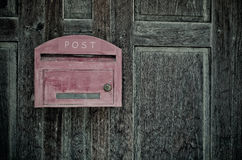 Grunge red wooden mail box on grunge wooden wall Stock Photo