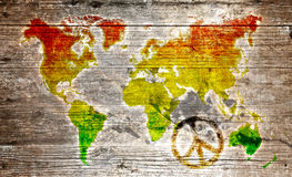 Grunge reggae world map. World map in reggae colors on textured wooden background with peace symbol royalty free stock images