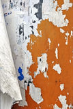 Grunge Ripped Poster Wall. Orange wall with layers of ripped posters Royalty Free Stock Images