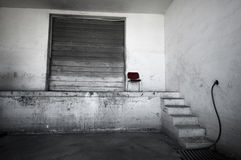 Grunge room with large door. A red chair in a white grungy room with a large garage door on a stage area Stock Photography